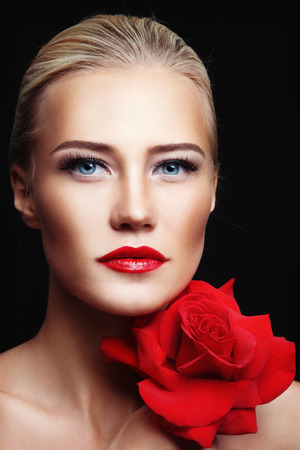 Portrait of young beautiful woman with red lipstick and rose in her hands photo