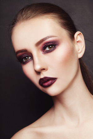 Portrait of young beautiful woman with stylish dark eyeshadow and lipstick photo