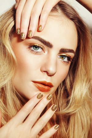 highlights: Portrait of young beautiful girl with golden make-up and fancy wild manicure