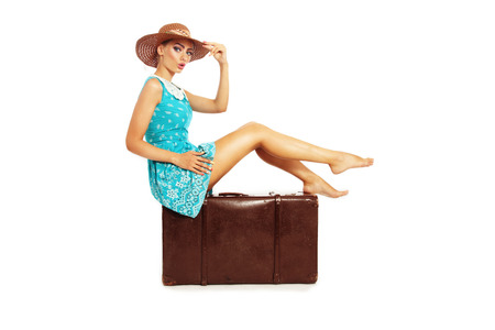 Beautiful sexy tanned barefoot pin-up girl in stylish dress and hat sitting on big vintage bag over white background Stock Photo