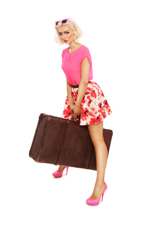 hot pink: Beautiful sexy blonde pin-up girl in mini skirt and hot pink shoes holding in her hands big heavy vintage bag over white background
