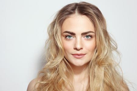 Retrato de la hermosa joven con el pelo largo desordenado y limpio maquillaje