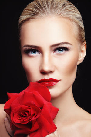 facelift: Portrait of young beautiful woman with red lipstick and rose in her hands