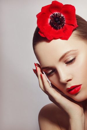 Vintage style portrait of young beautiful woman with red lipstick and flower in her hair