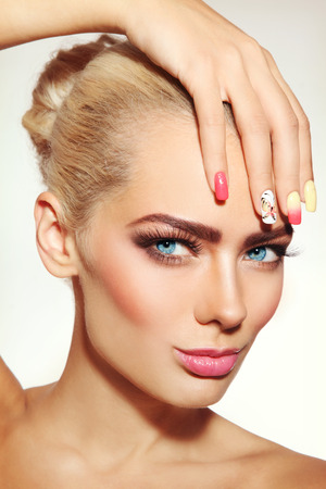 Close-up portrait of young beautiful blonde woman with stylish fresh make-up and fancy manicure Stock Photo