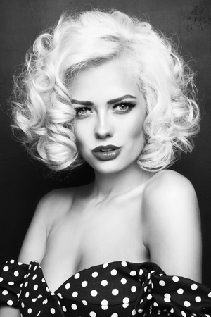 Black and white vintage style portrait of young beautiful sexy blonde pin-up girl with curly hair over grunge background