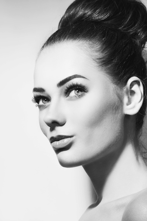 cheekbones: Black and white portrait of young beautiful girl with stylish make-up and hair bun looking upwards, copy space