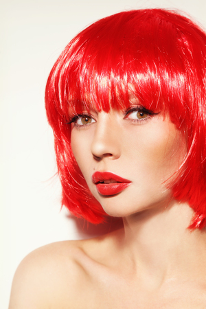 Portrait of young beautiful sexy red-haired girl with bob haircut and red lipstick photo