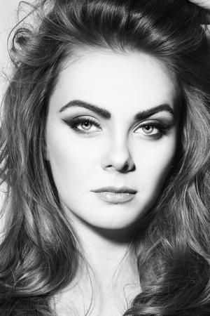 cabello rizado: retrato en blanco y negro de la joven y bella chica con estilo del ojo alado maquillaje y pelo rizado largo Foto de archivo
