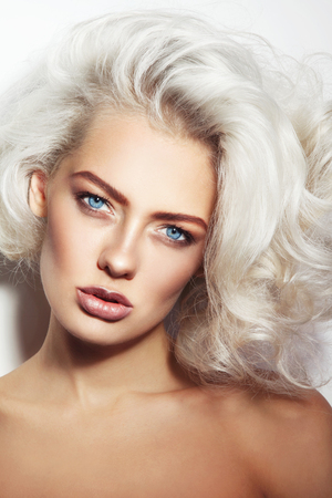 platinum hair: Portrait of young beautiful tanned woman with stylish make-up and platinum blonde curly hair Stock Photo