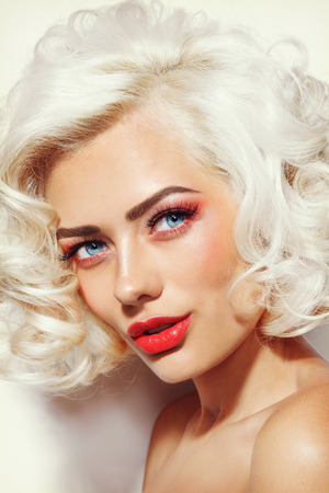 platinum hair: Vintage style portrait of young beautiful sexy platinum blonde pin-up girl with curly hair and red lips Stock Photo