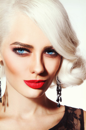 permanent wave: Portrait of young beautiful blonde tanned woman with stylish vintage hairdo and matte red lipstick
