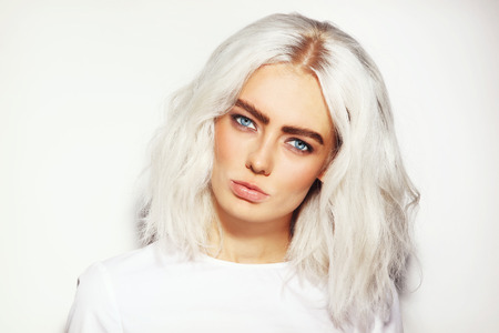 platinum hair: Portrait of young beautiful platinum blond woman with bold eyebrows