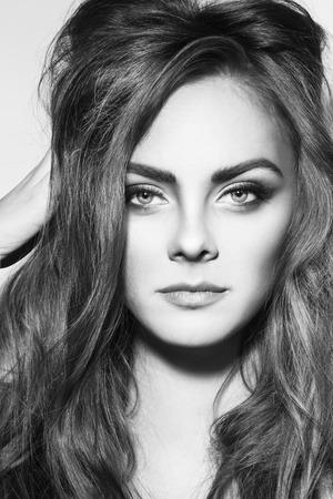 maquillaje de ojos: retrato en blanco y negro de la joven y bella chica con estilo del ojo alado maquillaje y pelo rizado largo Foto de archivo