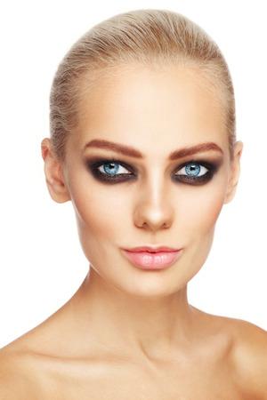 maquillaje de ojos: Primer plano retrato de la joven mujer atractiva rubia con ojos ahumados de estilo de maquillaje sobre el fondo blanco Foto de archivo