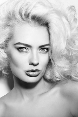 platinum hair: Black and white portrait of young beautiful woman with stylish make-up and platinum blonde curly hair Stock Photo