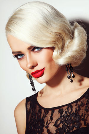 blond girl: Portrait of young beautiful blonde tanned woman with stylish vintage hairdo and matte red lipstick