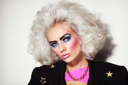 大胆な眉毛を持つ若い美しいプラチナ ブロンドの女性の肖像画と 80 年代風メイク 写真素材
