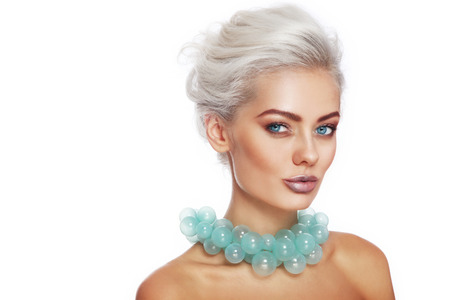 platinum hair: Portrait of young beautiful blonde woman with stylish make-up and hairdo and fancy glass necklace over white background