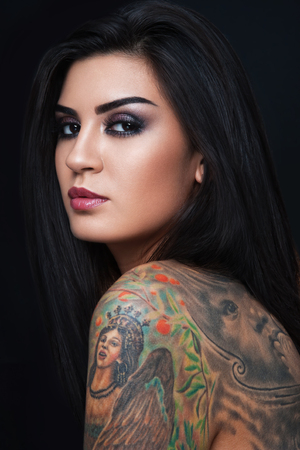Portrait of young beautiful sexy woman with gorgeous tattoo on her body