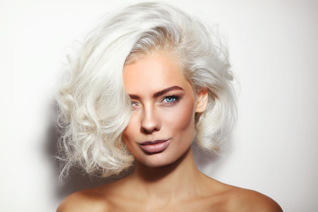 Portrait of young beautiful tanned platinum blonde woman with clean make-up