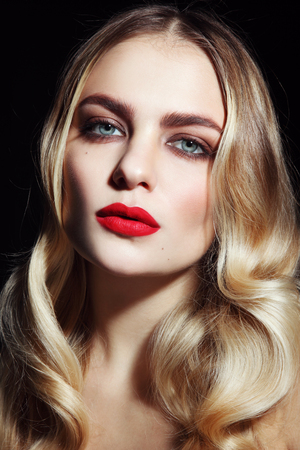Portrait of young beautiful glamorous woman with red lipstick and blonde curly hair