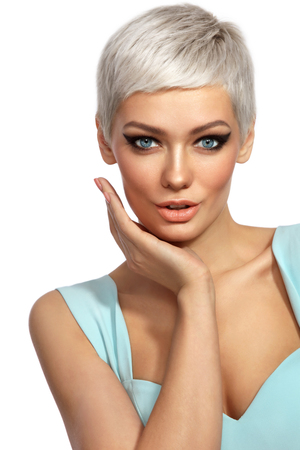 Young beautiful tanned woman with stylish cat eye make-up and platinum blonde hair touching her face over white background, copy space