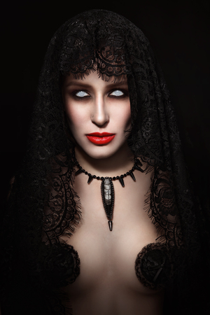 Vintage style portrait of young beautiful woman with zombie Halloween make-up and white contactl lenses photo