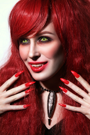 Vintage style portrait of young beautiful redhead woman with gothic Halloween make-up and fangs Stock Photo