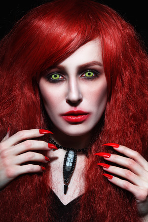 Vintage style portrait of young beautiful redhead woman with gothic Halloween make-up photo