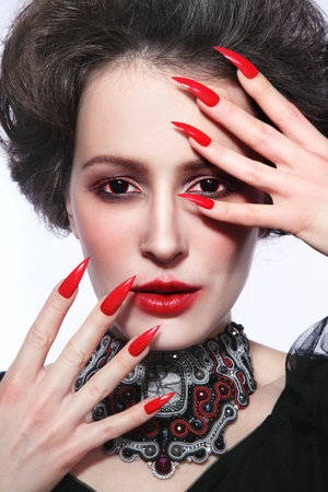 Vintage style portrait of young beautiful woman with gothic make-up and fancy contact lenses photo