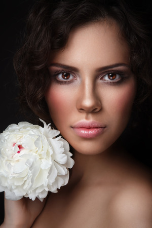 Young beautiful tanned woman with white peony