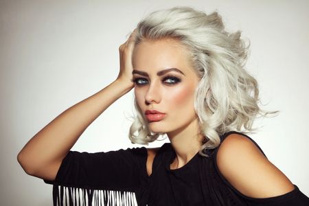 Vintage style portrait of young beautiful platinum blond woman with smoky eyes make-up Фото со стока