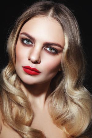 Jonge mooie glamoureuze vrouw met rode lippenstift en blond krullend haar Stockfoto