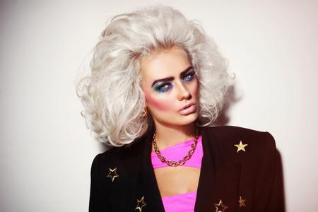 Portret van jonge mooie platina blonde vrouw met gewaagde wenkbrauwen en 80s stijlmake-up Stockfoto