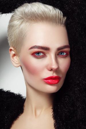 赤のマスカラー、口紅で若い美しいプラチナ ブロンドの魅力的な女性