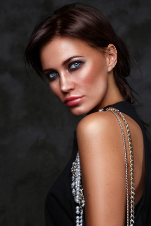Beautiful young slim tanned woman with smoky eye make-up