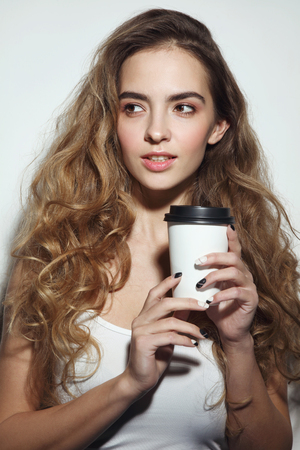 Young Beautiful Girl With Long Curly Hair And Cup Of Coffee In Her