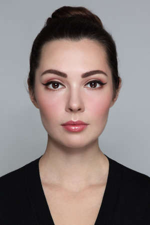 Jeune belle femme avec le maquillage élégant d'oeil de chat