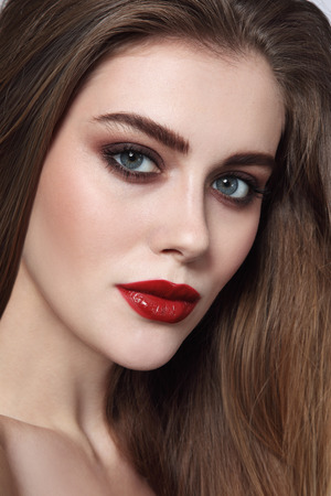 Portrait of young beautiful girl with smoky eye makeup and red lips