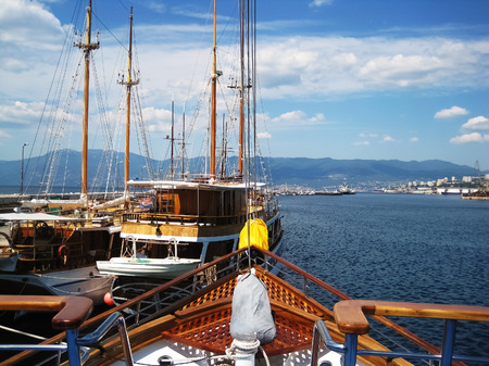 View from bow on few old sailboats and industrial part of city Rijeka at sunny day