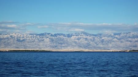 Long Velebit mountain behind low,desert island Pag