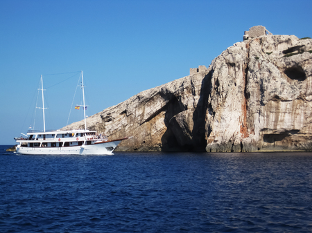 White cruise sailing ship near the huge cliff in national park Kornati in croatia at sunny afternoon