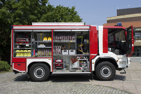 Red fire truck with open door and all his equpment on hot summer day|Cakovec Stock Photo