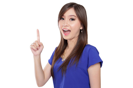 Beautiful young Asian woman pointing finger up and expressing happiness, on isolated white background