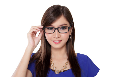 geeky: Beautiful young Asian woman smiling to camera while holding her dark framed glasses, on isolated white background Stock Photo