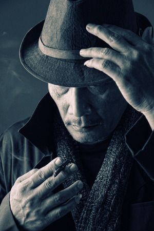 Vintage style portrait of old time secret agent smoking a cigarette while holding his fedora hat