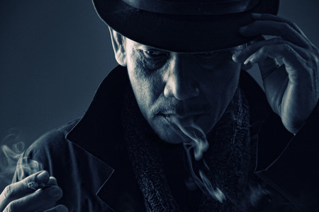 cold blooded: Vintage photo of cold blooded assassin adjusting his hat while smoking cigarette Stock Photo