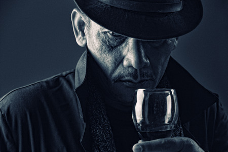 Portrait of an old gangster with mysterious face expression in darkness