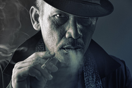 Portrait of evil crime lord with vicious eye smoking a cigarette, in HDR Stock Photo